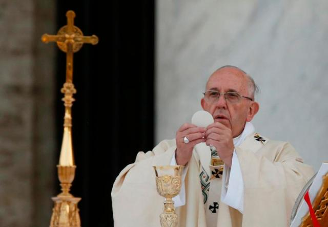 Pope Francis raises the Eucharist